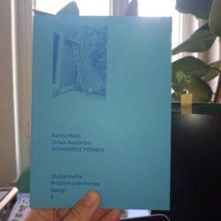 Das Heft Schwierige Formen mit hellblauem Cover vor den Pflanzen