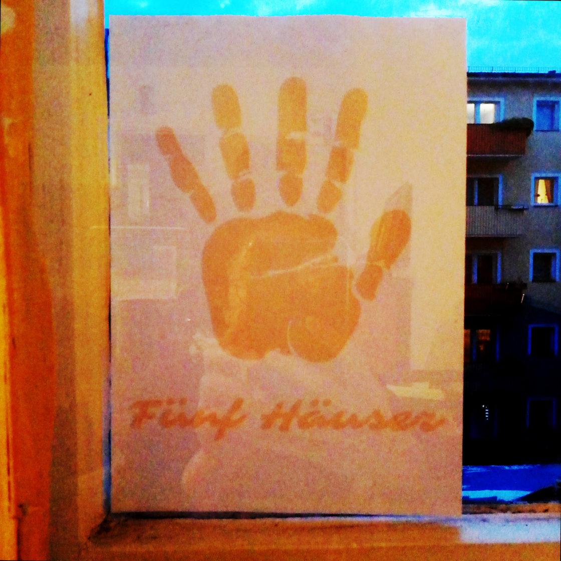 Das Logo von Fünf Häuser Initiative, offenes Handfläche, als Plakat, geklebt am Fenster