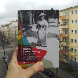 book, Rosa Luxemburg in Berlin hold with a left hand, in front of pale yellow building with many windows. On the cover, Rosa Luxemburg in summer dress and hat walking on a street