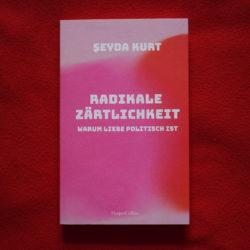 """Auf dem roten weichen Stoff liegt das Buch """"Radikale Zärtlichkeit"""" von Şeyda Kurt. Das buch hat hell rosa cover, etewas dunklere pinke Kreis vom links, rote Kreis vom rechts, beide etwas verschwommen und verschmelzen ineinander"""