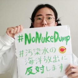 """Aiko hält ein Schild mit den grünen Schriften #NoNukeDump, #汚染水の海洋放出に反対します mit einem gelben Aufkleber """"Gegen Atomkraft"""" Für erneuerbare Energie"""" in der Mitte rote zackig rundes Gesicht mit gehobenem Faust"""