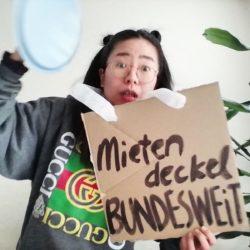 """Aiko hält ein hellblaues Kochtopfdeckel mit dem rechten Hand über kopf, vom Hals hängt sie ein Schild """"Mietendeckel BUNDESWEIT"""". Ihre Augen sind weit geöffnet. Im Hintergrund ein Paar Blätter vom Baum."""