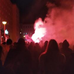 eine Straße mit viele Menschen von hinten, in der Mitte brennt sehr hell und große Rauch steigt. Links und vorne Hochhäuser