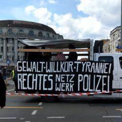 """blauer Himmel, Wolke kommen von rechts. 3.5t LKW mit Transparent """"Gewalt, Willkür, Tyrannei. Rechtes Netzwerk Polizei"""""""