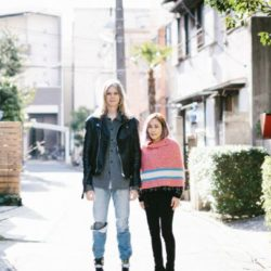 Elin McCready and Midori Morita standing in a surbian street in Japan, full of lights. Elin wears black leather jacket and jeans. She is tall and has silver long hair. Midori has pink knit poncho with light blue and white stripe below with black skinny pants. She has blond shoulder length hair, is high as shoulder of Elin. by Yasuyo Tadokoro