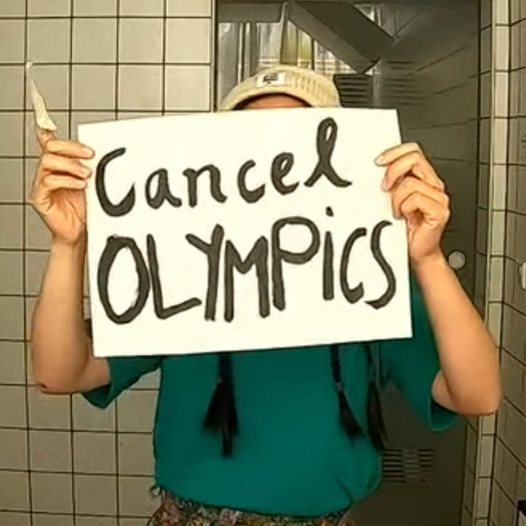 """A person holds paper """"Cancel Olympics"""""""