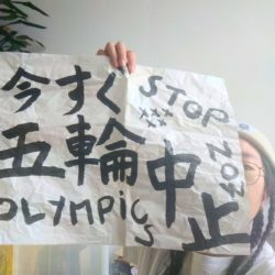 a person holding paper 今すぐ五輪中止 stop olympics now, looking from the side of the paper on the right corner