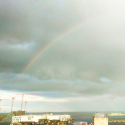 rainbow over the clouds. below in picture some red cranes, some buildings and ocean, a ship comes from right.
